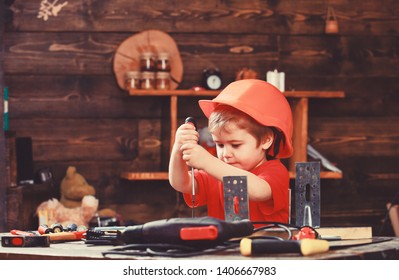 Childhood concept. Kid boy in orange hard hat or helmet, study room background. Boy play as builder or repairer, work with tools. Child dreaming about future career in architecture or building.