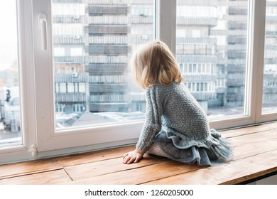 Childhood concept. Little girl sitting near window at home.