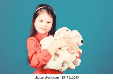 Childhood concept. Small girl smiling face with toys. Happy childhood. Little girl play with soft toy teddy bear. Lot of toys in her hands. Collecting toys hobby. Cherishing memories of childhood.