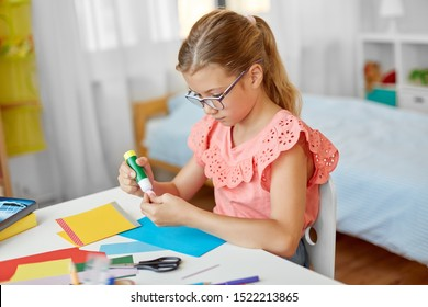 childhood, creativity and hobby concept - creative girl making greeting card and sticking pompon with glue stick at home