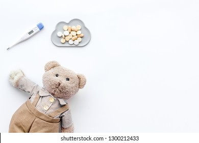 Childhood diseases concept. Treatment of children.Teddy bear toy, thermometer and pills on white background top view copy space