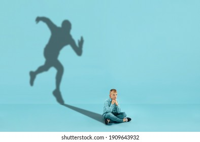 Childhood and dream about big and famous future. Conceptual image with boy and shadow of sportive male runner, champion on blue background. Childhood, dreams, imagination, education concept.