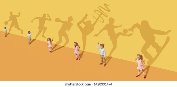 Childhood and dream concept. Conceptual image with children and shadow on the yellow studio wall. Little girl and boy want to become gymnast, dancer, artist, boxer, runner or football player.