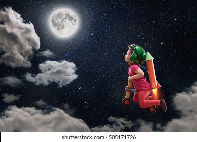A childhood dream, the cute little girl flying to the moon on her bike, she wears a helmet and has made a cardboard rocket hooked on her back