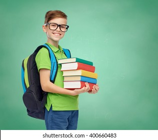 childhood, education and people concept - happy smiling student boy in eyeglasses with school bag and books over green school chalk board background