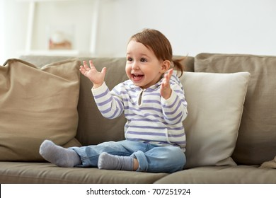 childhood, emotions and people concept - happy smiling baby girl sitting on sofa and clapping hands at home