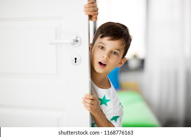 childhood, emotions and people concept - surprised little boy behind door at home