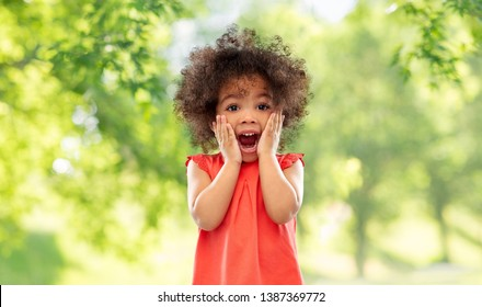 childhood, expressions and emotions concept - surprised or scared little african american girl screaming over green natural summer background
