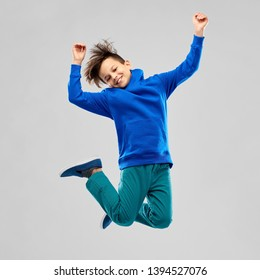 childhood, expressions and people concept - portrait of smiling boy in blue hoodie jumping over grey background