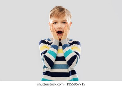 childhood, expressions and people concept - shocked little boy in striped pullover touching his face over grey background