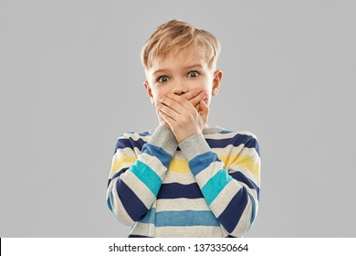 childhood, expressions and people concept - shocked little boy in striped pullover closing his mouth by hands over grey background