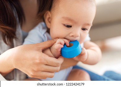 childhood and family concept - close up of asian baby boy with mother