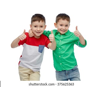 childhood, fashion, friendship and people concept - happy smiling little boys showing thumbs up