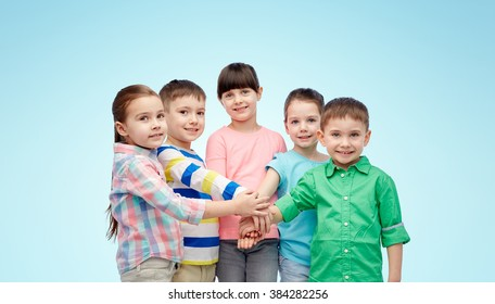 childhood, fashion, friendship and people concept - happy little children with hands on top over blue background