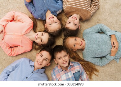 childhood, fashion, friendship and people concept - happy smiling children lying on floor in circle