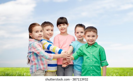 childhood, fashion, friendship and people concept - happy little children with hands on top over blue sky and grass background