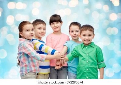 childhood, fashion, friendship and people concept - happy little children with hands on top over blue holidays lights background
