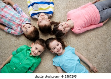 childhood, fashion, friendship and people concept - group of happy smiling little children lying on floor