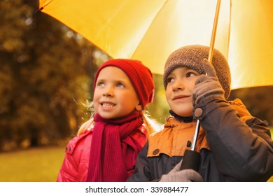 childhood, friendship, season, weather and people concept - happy little boy and girl with umbrella in autumn park