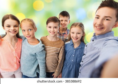 childhood, friendship, technology and people concept - happy children talking selfie over green lights background
