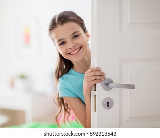 childhood, fun and people concept - happy smiling beautiful girl behind door at home