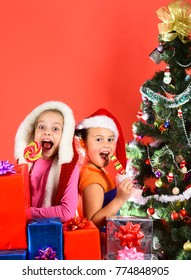 Childhood and happiness concept. Kids in Santa hats with gift boxes and lollipops. Girls celebrate Christmas together eating sweets. Children with excited faces on red background.