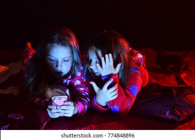 Childhood and happiness concept. Schoolgirls have pajama party. Girls in pajamas play with phone on dark background. Children with interested faces lie on bed.