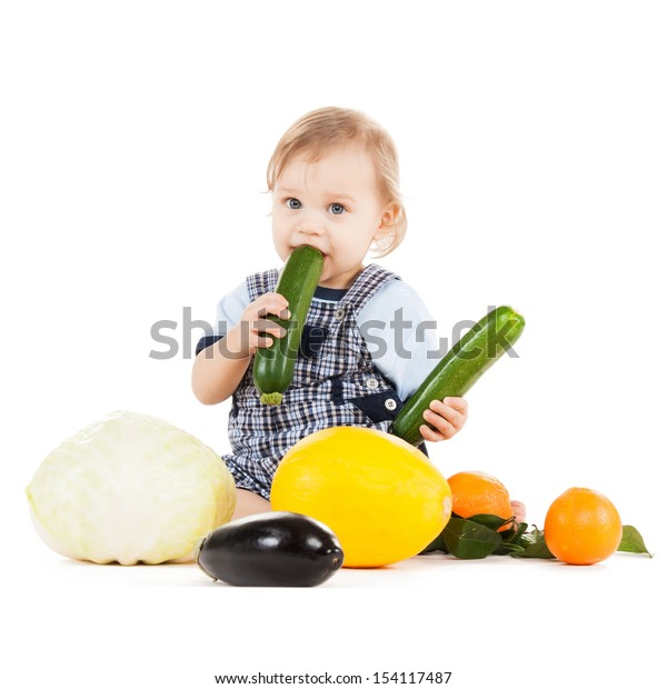 childhood and healthy food concept - cute toddler with vegetables and fruits eating squash
