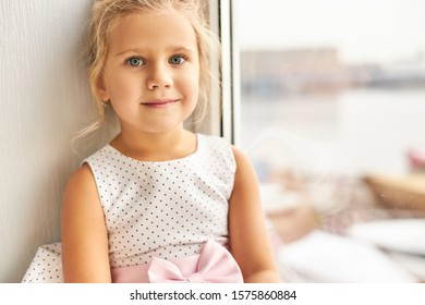 Childhood and innocent concept. Portrait of charming cute little girl with gathered fair hair and big beautiful eyes sitting by window having happy facial expression, looking at camera and smiling