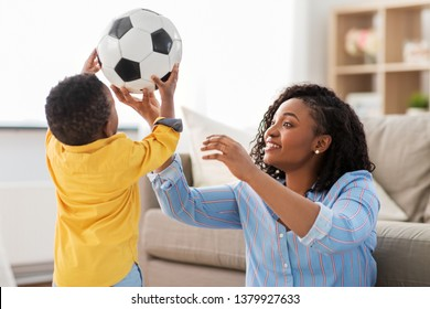 childhood, kids and people concept - happy african american mother and her baby son playing with soccer ball together on sofa at home