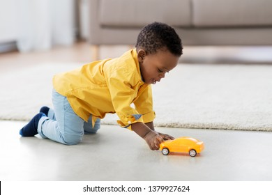 childhood, kids and people concept - lovely african american baby boy playing with yellow toy car on floor at home