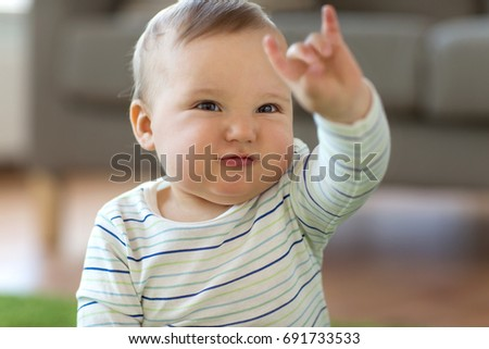 childhood, kids and people concept - lovely baby boy showing rock hand sign at home