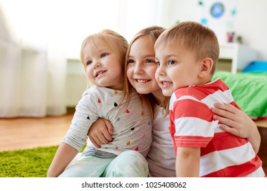 childhood, leisure and family concept - happy little kids hugging at home