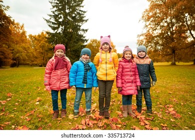 childhood, leisure, friendship and people concept - group of happy kids in autumn park