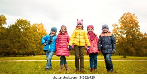 childhood, leisure, friendship and people concept - group of happy children holding hands in autumn park