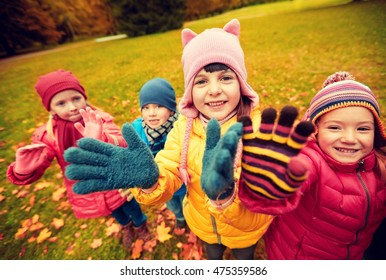 childhood, leisure, friendship and people concept - group of happy children waving hands in autumn park
