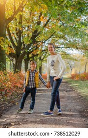 Childhood, leisure, friendship and people concept - Two happy kids having fun in autumn park