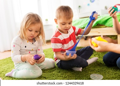 childhood, leisure and people concept - children playing with modelling clay or slimes at home