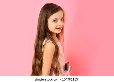 Childhood, look, happiness, hairstyle. Small girl child model in beautiful dress. Little girl with long hair on pink background. Kid fashion, hairdresser, birthday. Beauty and fashion, punchy pastels.