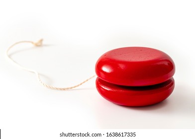 Childhood memories, nostalgia and vintage wood toy concept with red retro wooden yoyo isolated on white background