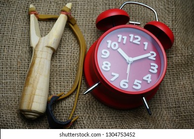 Childhood memories of time. A slingshot toy with red clock on brown rags.
