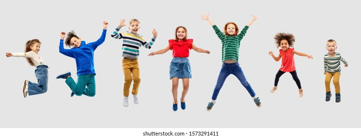 childhood, motion and happiness concept - happy little children jumping in air over grey background
