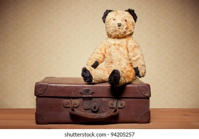 Childhood Nostalgia Teddy Bear. Old vintage teddy bear and leather suitcase with copyspace.
