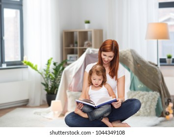 childhood, parenting and relationship concept - happy mother with adorable little daughter reading book at home over kids room and tepee background
