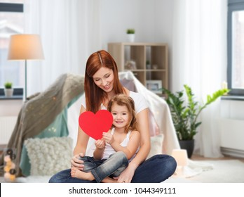 childhood, parenting and relationship concept - happy mother with adorable little girl and red heart over kids room and tepee background