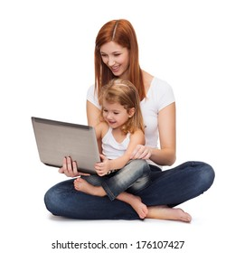 childhood, parenting and technology concept - happy mother with adorable little girl with laptop