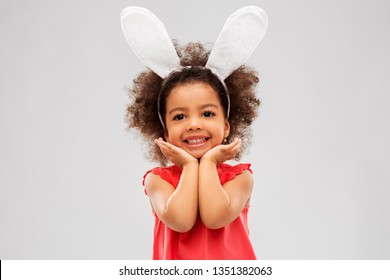 childhood, party props and easter concept - happy little african american girl wearing bunny ears headband posing over grey background