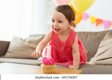 childhood, people and celebration concept - happy baby girl with cupcake on birthday party at home