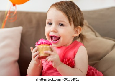 childhood, people and celebration concept - happy baby girl eating cupcake on birthday party at home