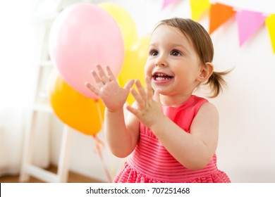 childhood, people and celebration concept - happy baby girl on birthday party at home